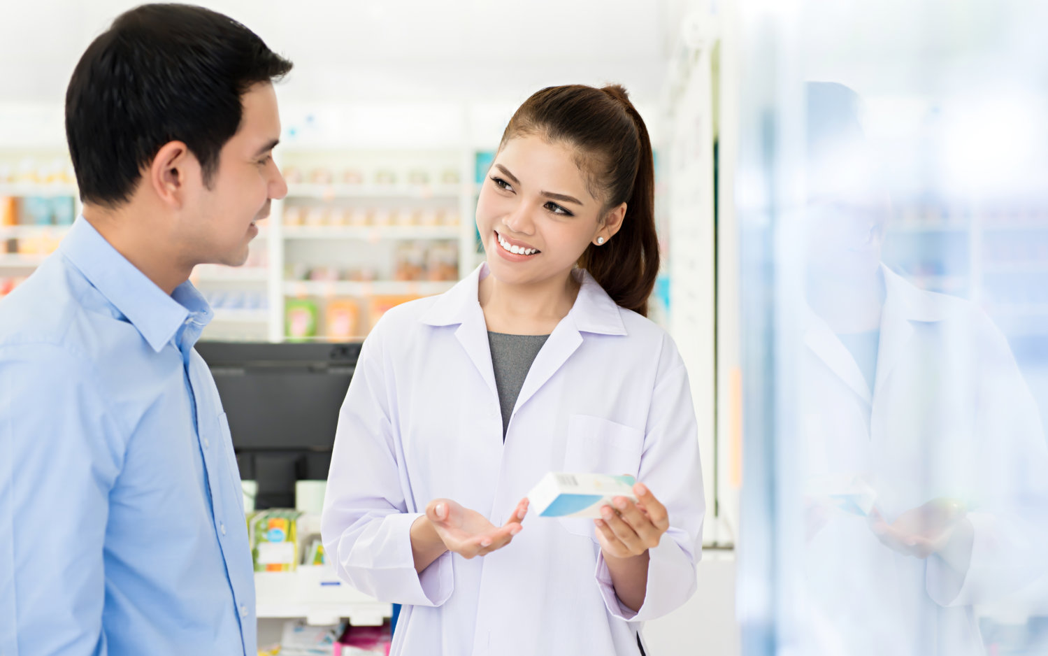 Pharmacist consulting a men in a wheelchair in pharmacy